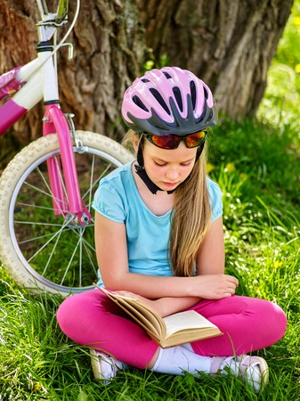 biker girl: Bikes cycling girl. Girl rides bicycle. Girl in cycling sitting on green grass near bicycle and read book on rest near bicycle. Cycling is good for health.
