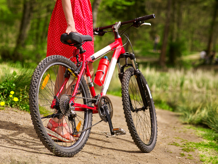 ecotourism: Bikes cycling girl. Body part of girl wearing red polka dots dress rides bicycle into park. Girl in ecotourism. Cycling is good for health. Cyclist is unrecognizable.