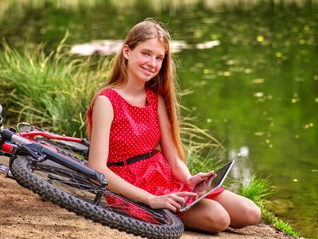 lunares rojos: Bikes cycling girl. Girl wearing red polka dots dress recreation near bicycle into park. Child watch tablet pc. Girl in ecotourism.
