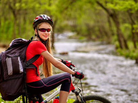 biker girl: Bikes cycling girl. Girl with big rucksack rides bicycle. Girl cycling fording throught water . Cycling trip is good for health. Cyclist is looking at camera.