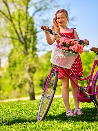 lunares rojos: ni�a de la bicicleta del ni�o que lleva lunares rojos vestido de paseos en bicicleta en el parque de verano. Foto de archivo