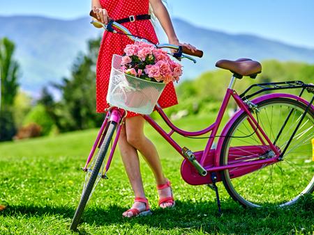 lunares rojos: Cuerpo de la niña de la bicicleta pieza de desgaste lunares rojos vestido de paseos en bicicleta en el parque. Foto de archivo