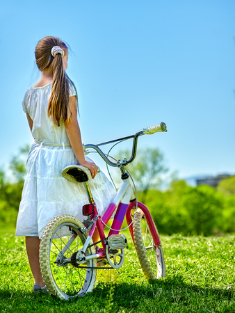 blu sky: Bikes bicycle girl. Child girl wearing white skirt looks into distance keeps bicycle. Blu sky and green tree on background. Summer park outdoor.