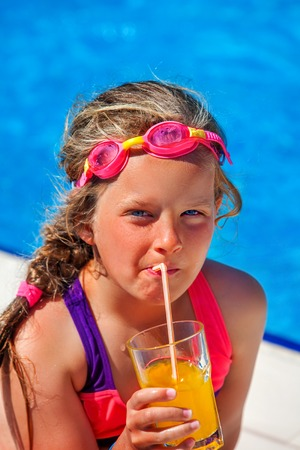 Child in swimsuit and goggles drinks orange squeezed juice in swimming pool into water park. Summer swimming holiday.Outdoor.