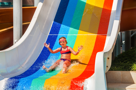 8 years: Child girl 8 years slide down the water slide at aquapark . Different colors painted childrens slide. Summer water park holiday. Outdoor. Stock Photo