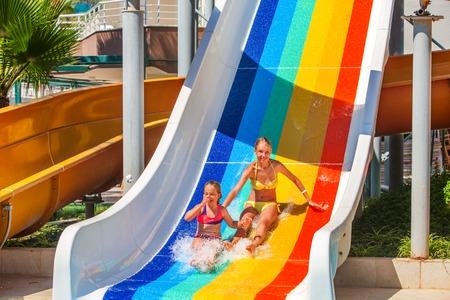 water   slide: Two different ages children at aquapark slide down water slide. Summer aquapark holiday. Outdoor water slide. Stock Photo