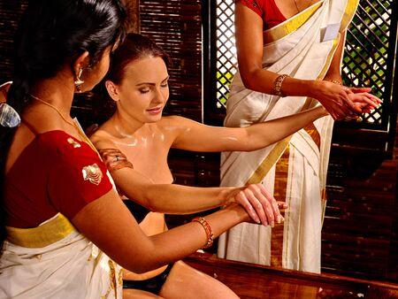 panchakarma: Seminude white woman having pouring oil massage in spa Indian massage salon.