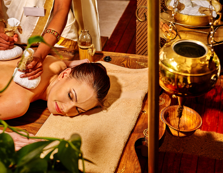 spa treatment: Woman lie on stomach having ayurvedic massage with pouch of rice. Shirodhara pot for head massage on foreground.