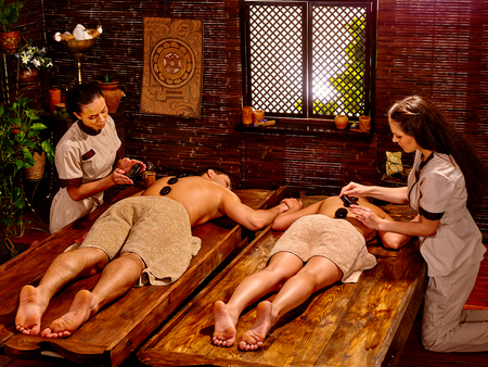 lastone: Couple lays her head to window having stone massage. Ayurveda lastone spa treatment.