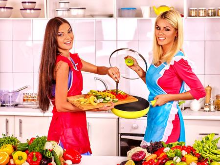 mandil: Dos amigos de las mujeres que se preparan los alimentos en la cocina. Vegetariana preparar en la cocina.