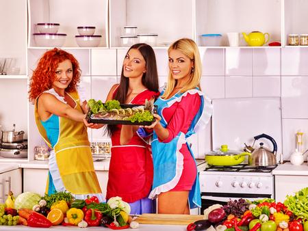 prepare: Happy group women prepare fish in oven. Seafood fish prepare.