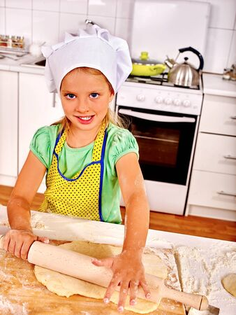 knead: Child girl wearing cooking hat cooking knead dough at kitchen.