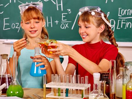 chemistry class: Happy children holding chemistry flask in chemistry class. Stock Photo