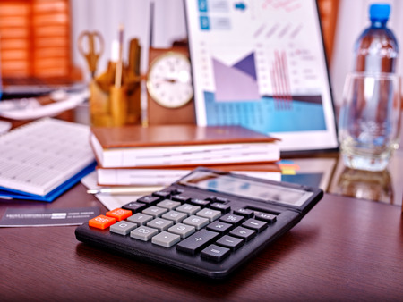office life: Business still life with calculator on table in office. There are business stuff on foreground.