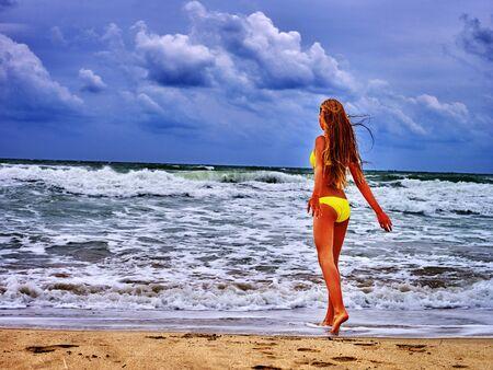 ragazze a piedi nudi: mare ragazza di estate. Ragazza in costume da bagno sulla spiaggia vicino mare con le onde. La ragazza va spiaggia e le onde ammirando. Archivio Fotografico