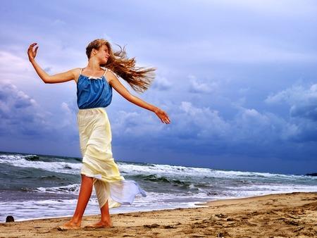 ocean and sea: Summer girl sea. Woman on beach near ocean with waves. Wind blew his hair. Girl enjoying bad weather on beach sea.