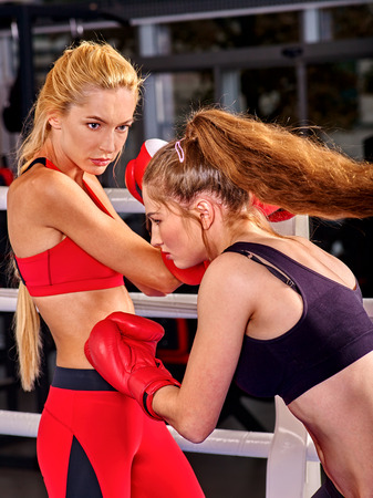 female boxing: Two boxing women wearing red boxing gloves are boxing on boxing ring. Stock Photo