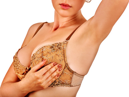 Woman in lingerie examines her breasts. Breasts in beautiful lace lingerie.