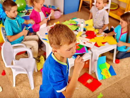 colored paper: Group kids creative with colored paper on table in kindergarten . Creative development of children.
