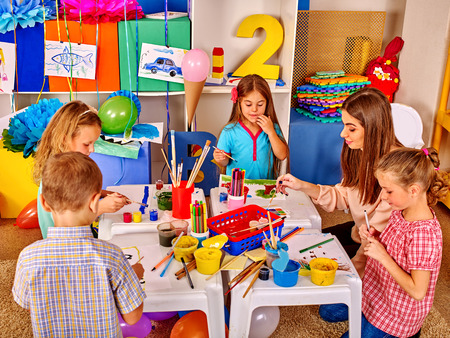 educator: Children with school teacher woman painting on paper at table in primary painting school . Stock Photo