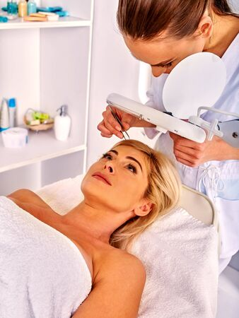 tweezing eyebrow: Woman middle-aged in spa salon with young beautician. Tweezing eyebrow by woman beautician. Stock Photo