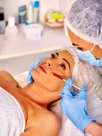 Mujer de mediana edad en el salón de spa con esteticista. Mujer de la belleza que da la inyección de botox. Inyección en los pliegues nasolabiales. Foto de archivo