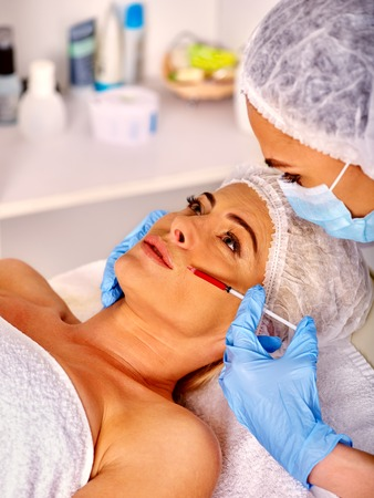 Woman middle-aged in spa salon with beautician. Beauty woman giving botox injection. Injection in nasolabial folds. Imagens