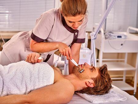 sound therapist: Man receiving electric facial peeling hydradermie at beauty salon.Man facial care.