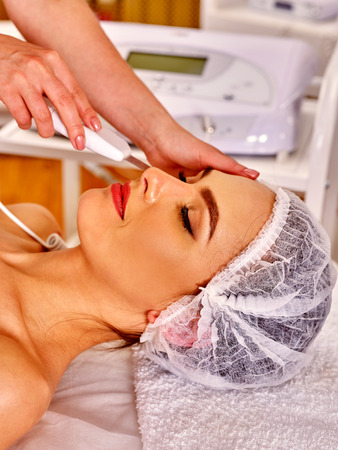 sound therapist: Woman receiving electric facial ultrusound peeling massage at beauty salon. Different types of facial massage.