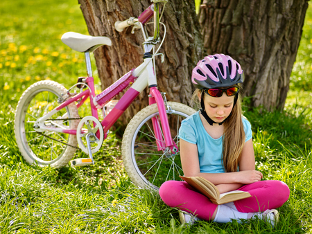 bicycling: Bicycling girl. Girl rides bicycle. Girl in bicycling helmet read book on rest near bicycle. Bicyclist looking at book.