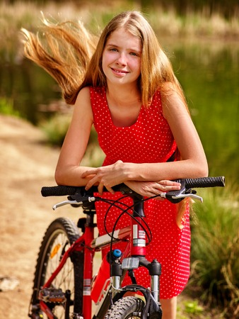 red polka dots: Bicycle girl. Girl wearing red polka dots dress rides bicycle into park. Girl in ecotourism. Bicycle is good for health. Bicycle girl have a long blond hair. Foto de archivo
