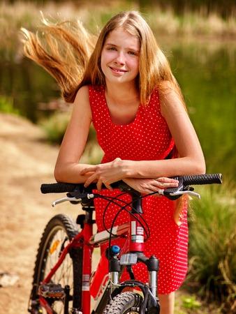 lunares rojos: chica de la bicicleta. Ni�as el uso de lunares rojos visten paseos en bicicleta en el parque. Chica en el ecoturismo. Bicicleta es bueno para la salud. chica de la bicicleta tiene un largo cabello rubio.