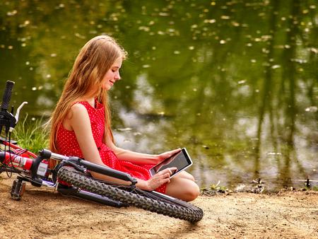 lunares rojos: chica de la bicicleta. La muchacha que desgastan los lunares rojos visten de recreación cerca de la bicicleta en el parque reloj de la PC de la tableta. La muchacha se sienta cerca del agua.