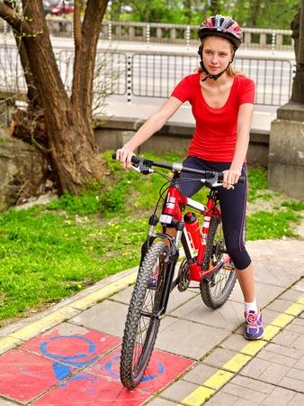 bike lane: Bicycle girl. Girl wearing bicycle helmet and glass bicycle. Girls cycling on yellow bike lane. Bike share program save money and time at city street.