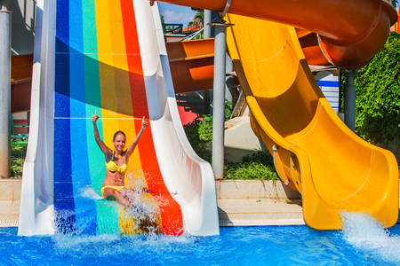 aqua park: Child on water slide at aquapark show thumb up. There are some water slides with flowing water in aqua park. Summer water park holiday. Outdoor.