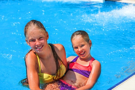 plummet: Two different ages children hugging and looking up swim in swimming pool. Summer swimming holiday. Outdoor swimming pool. Children activities lifestyle.