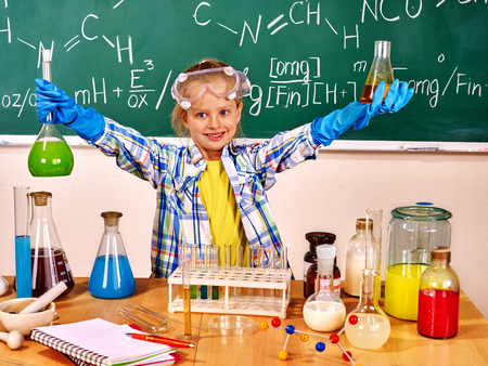 chemistry class: Child in glove holding flask in chemistry class.