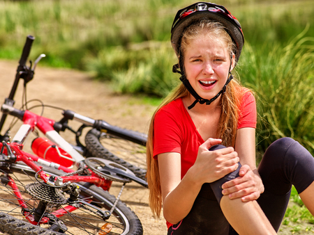 hurt: Bikes cycling girl. Girl rides bicycle. Girl girl fell off bicycle. Bicycle girl keeps self for bruised knee.