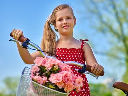lunares rojos: Bicicletas Ciclo de la muchacha. La muchacha del niño que lleva lunares rojos vestido de paseos en bicicleta con flores canasta. Las montañas y el cielo azul en el fondo.