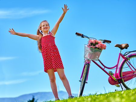 blu sky: Bikes cycling girl. Child girl wearing red polka dots dress rides bicycle with flowers basket. Mountains and blu sky on background. Stock Photo