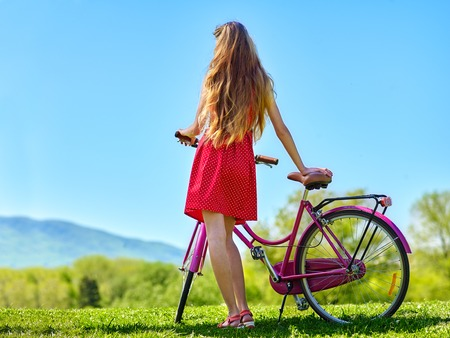 view girl: Bikes bicycle girl. Teenager girl wearing red polka dots dress looking into distance keeps bicycle with flowers basket. Green grass. Back view. Stock Photo