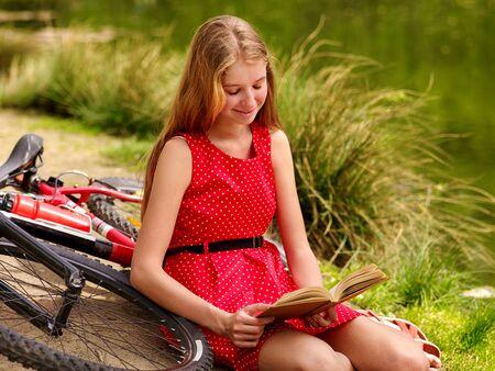 lunares rojos: Bicicletas Ciclo de la muchacha. Niñas el uso de lunares rojos visten paseos en bicicleta en el parque. La muchacha leyó el libro. La muchacha se sienta apoyado en bicicleta en la orilla Foto de archivo