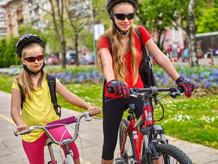 bike lane: Bikes bicyclist girl. Girls wearing bicycle helmet with rucksack ciclyng bicycle. Girls children cycling on yellow bike lane. Bike share program save money and time.