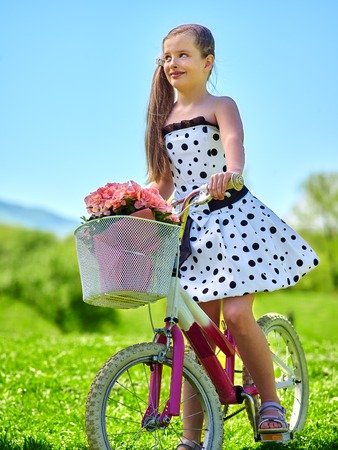 blu sky: Bikes cycling girl. Child girl wearing white polka dots dress rides bicycle with pink flowers basket. Green and blu sky on background. Stock Photo