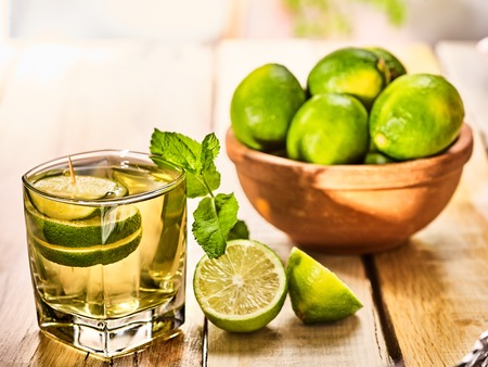 Country drink. On wooden boards is glass with green transparent drink and lime glue bowl. A drink number fifteen mojito with mint leaf on sunlight . Country life. Light background.