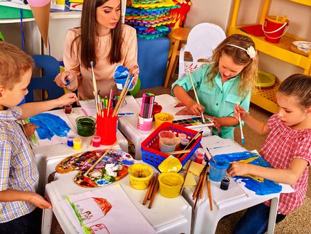 Kinderen schilderen op papier aan tafel op de basisschool. Leraar vrouw leren kinderen schilderen.