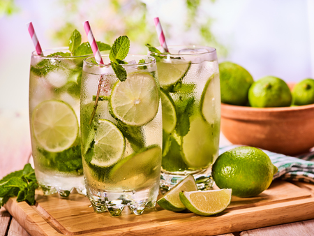 Alcohol drink. On wooden boards three glasses with alcohol drink and ice cubes. A drink number forty five cocktail mohito with straw and lime and mint leaf. Country life. Outdoor. Light background. Banco de Imagens