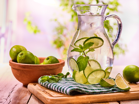 Country drink. On wooden boards is glass jug with transparent drink and lime glue bowl. A drink number thirty one with ice cubes . Country life. Light background. Reklamní fotografie