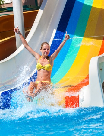 Child on water slide at aquapark shows thumb up two hands . There are some water slides with flowing water in aqua park. Summer water park holiday. Happy summer. Outdoor.