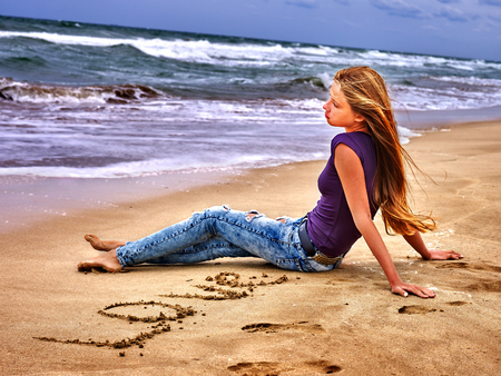 Mar de niña de verano. Chica dibujar palabra de amor en la arena en la playa del mar. Foto de archivo